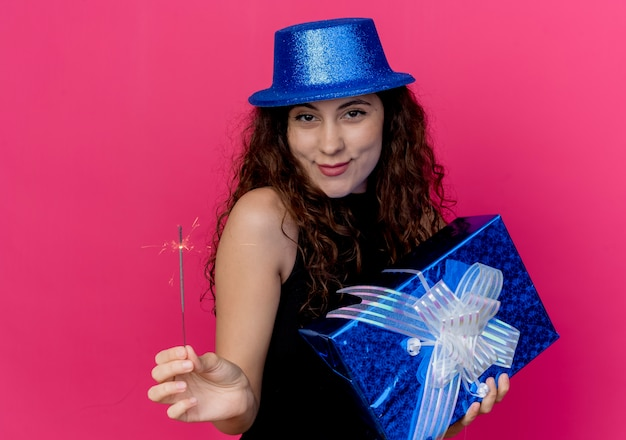 ピンクの壁の上に立っている誕生日プレゼントボックスとスパークラー幸せでポジティブな笑顔の誕生日パーティーのコンセプトを保持している休日の帽子で巻き毛の若い美しい女性 無料写真