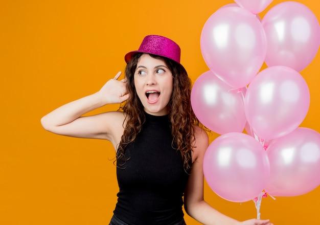 オレンジ色の壁の上に立っている陽気な誕生日パーティーのコンセプトを笑顔で幸せで興奮している気球の束を保持している休日の帽子で巻き毛の若い美しい女性 無料写真
