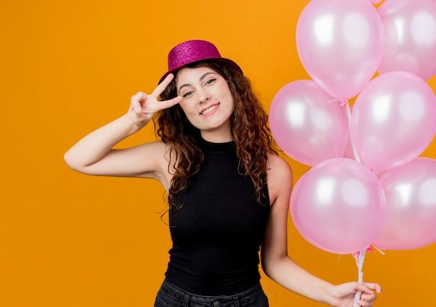 オレンジ色の壁の上に立っているvサインの誕生日パーティーのコンセプトを元気に見せて幸せで前向きな笑顔の気球の束を保持している休日の帽子で巻き毛の若い美しい女性 無料写真