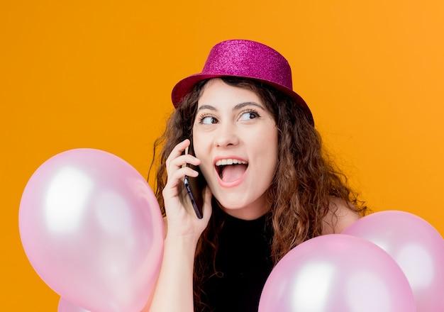 オレンジ色の壁の上に立っている携帯電話で幸せで興奮した誕生日パーティーのコンセプトを話している気球の束を保持している休日の帽子で巻き毛の若い美しい女性 無料写真