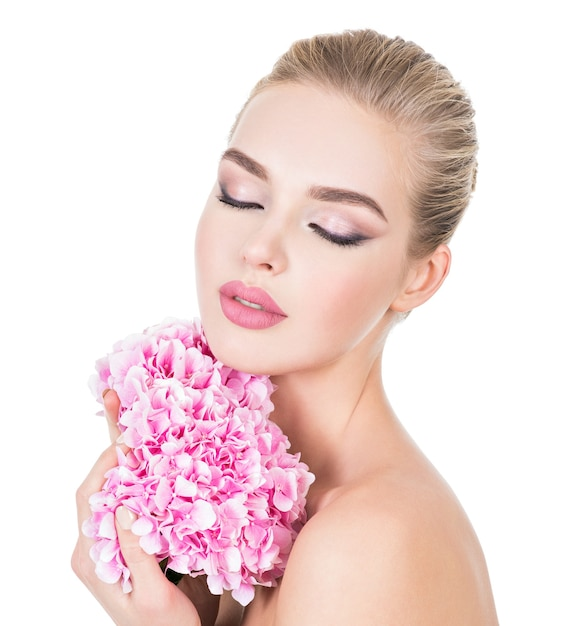 Young beautiful woman with flowers near face. Free Photo