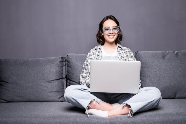 Молодая красивая женщина в очках с помощью портативного компьютера дома, сидя на диване Бесплатные Фотографии