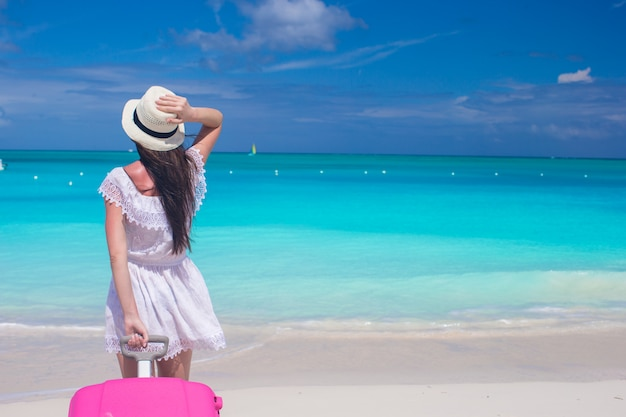 Young beautiful woman with large suitcase on tropical beach Premium Photo