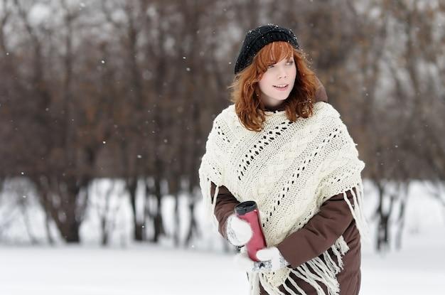 Young beautiful woman with metallic tumbler walking in winter park Premium Photo