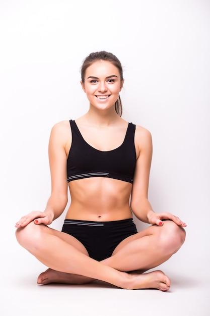 흰 벽에 고립 된 바닥에 앉아 검은 속옷에 완벽한 몸매를 가진 젊은 아름다운 여자 무료 사진