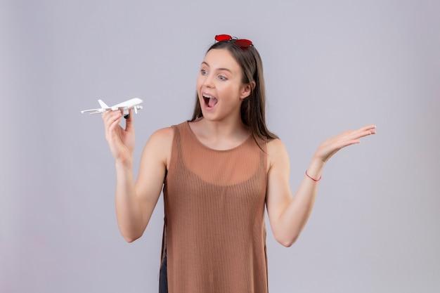 Giovane bella donna con occhiali da sole rossi sulla testa che tiene aeroplano giocattolo cercando in piedi giocoso e felice con il braccio alzato su sfondo bianco Foto Gratuite
