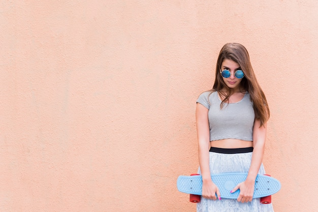 Young beautiful woman with skateboard on pink background Free Photo
