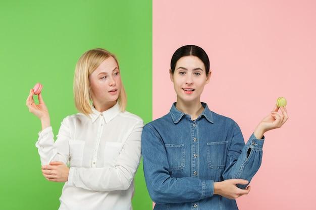 Giovani belle donne che tengono amaretti pasticceria nelle sue mani Foto Gratuite