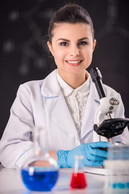 Young beauty female doctor researcher using microscope. Premium Photo
