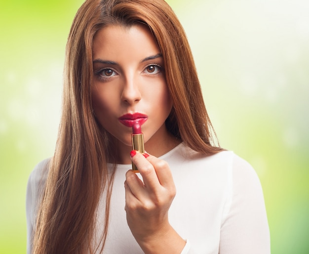 Young beauty with rose lipstick in hand. Free Photo