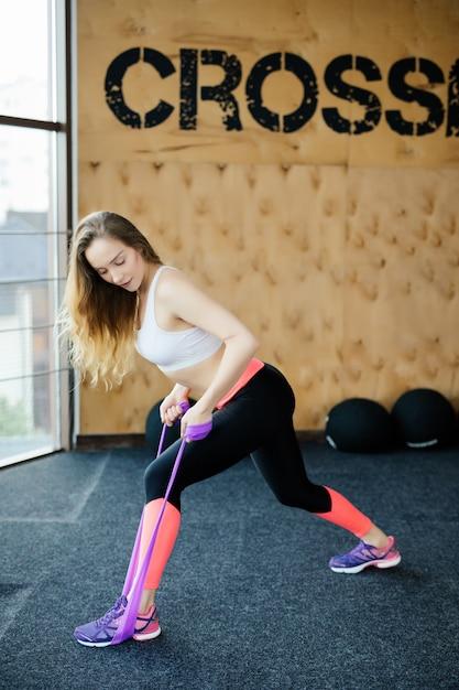 Donna giovane bellezza facendo esercizio con cinture elastiche in palestra Foto Gratuite