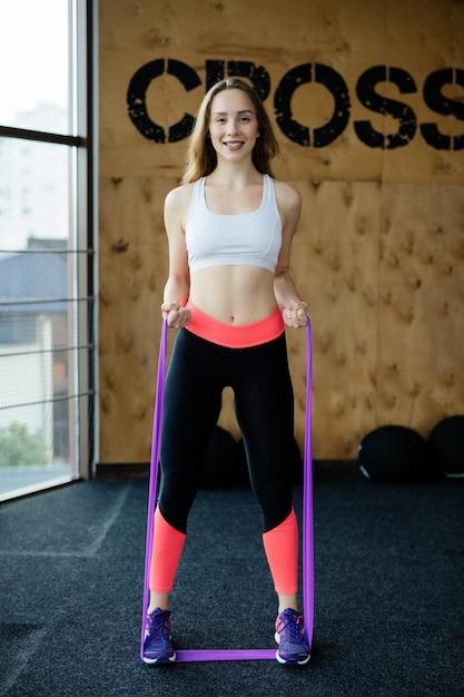 ジムでゴムベルトで運動をしている若い美容女性 無料写真