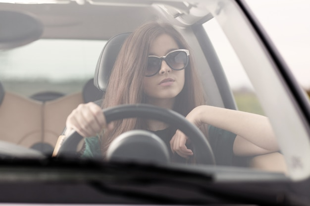 Young beuatiful woman driving a car Premium Photo