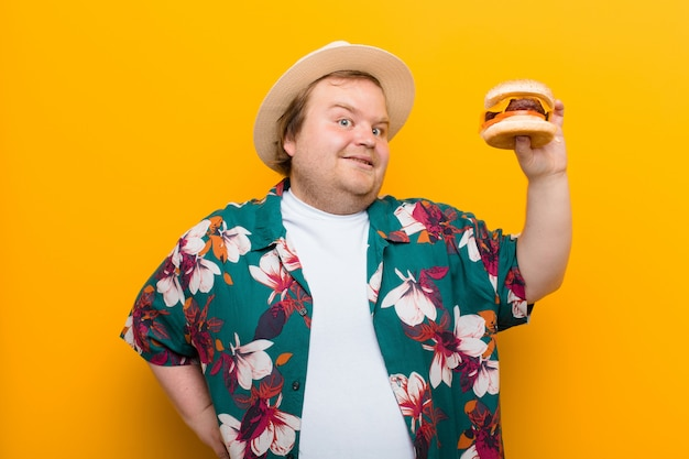 Young big size man with a cheese burger against flat wall Premium Photo