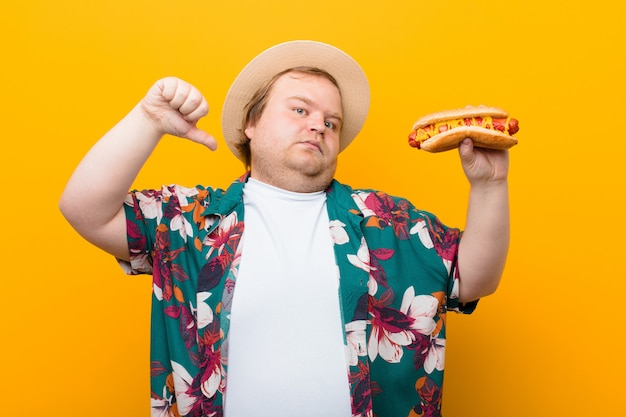 Young big size man with a hot dog against flat wall Premium Photo