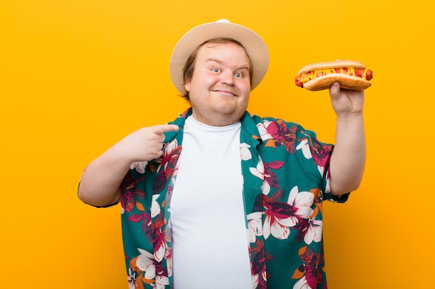 Young big size man with a hot dog  flat wall Premium Photo