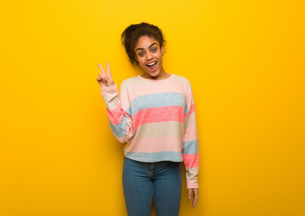 Young black african american girl with blue eyes doing a gesture of victory Premium Photo