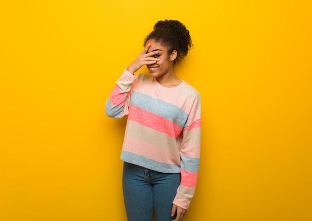 恥ずかしいと同時に笑っている青い目の若いアフリカ系アメリカ人少女 Premium写真