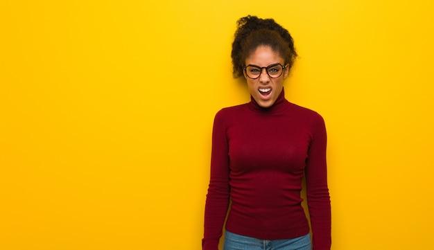 Молодая черная афроамериканская девушка с голубыми глазами кричит очень сердито и агрессивно Premium Фотографии