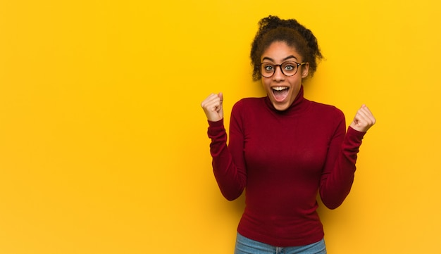 Young black african american girl with blue eyes surprised and shocked Premium Photo