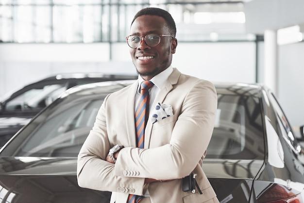 Young black businessman on auto salon. car sale and rent concept. Premium Photo