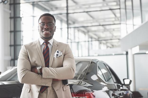 Young black businessman on auto salon. car sale and rent concept. Free Photo