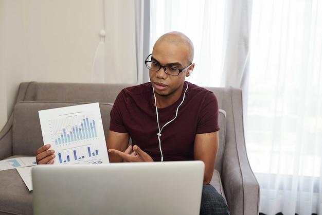 Молодой черный бизнесмен в наушниках посещает онлайн-конференцию и показывает финансовый отчет Premium Фотографии