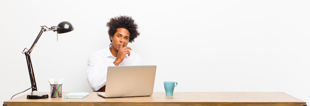 Young black businessman looking serious and cross with finger pressed to lips demanding silence or quiet, keeping a secret on a desk Premium Photo