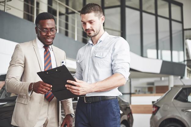 Una giovane donna d'affari nera firma i documenti e acquista una nuova automobile. il rivenditore di auto è in piedi accanto a lui. Foto Gratuite