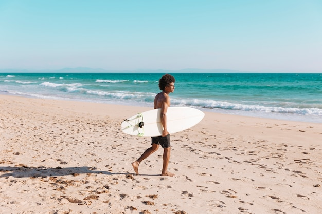 Young black male coming with surfboard to sea Free Photo