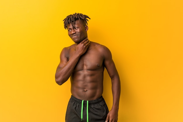 上半身裸の若い黒人男性が水着を着ていると、ウイルスや感染症が原因で喉の痛みを感じます。 Premium写真