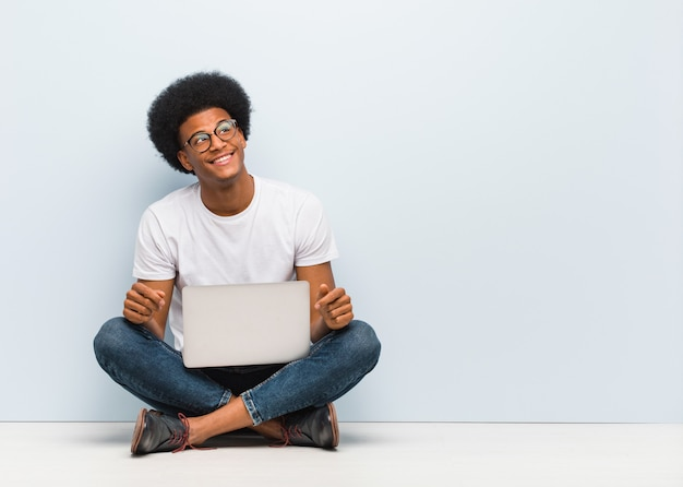 Young black man sitting on the floor with a laptop dreaming of achieving goals and purposes Premium Photo