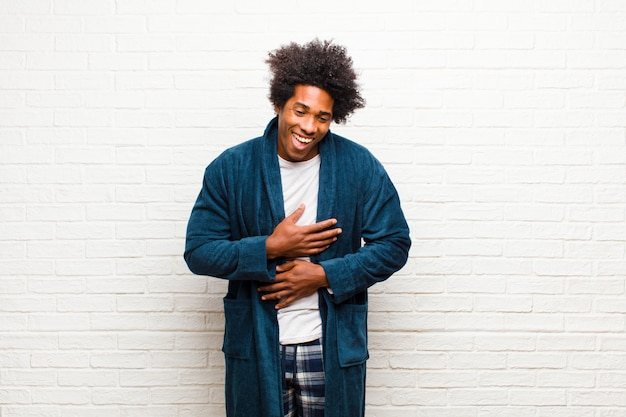 Young black man wearing pajamas with gown laughing out loud at some hilarious joke, feeling happy and cheerful, having fun against brick wall Premium Photo