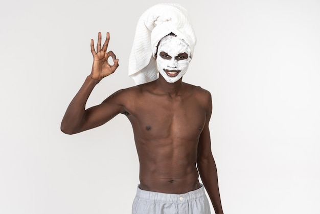 A young black man with a bath towel around his waist doing Premium Photo