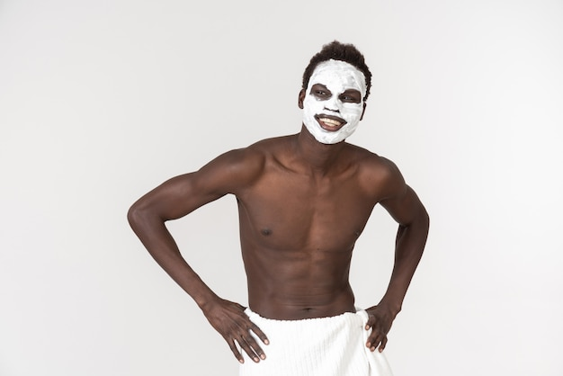 A young black man with a white bath towel around his waist going Premium Photo