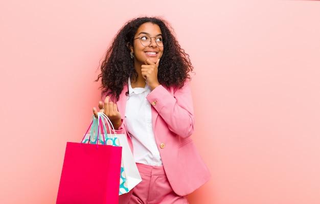 ピンクの壁に買い物袋を持つ若い黒きれいな女性 Premium写真