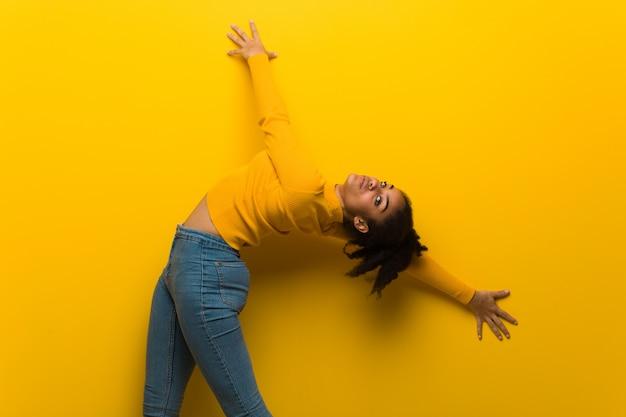 Young black woman dancing over an orange wall Premium Photo