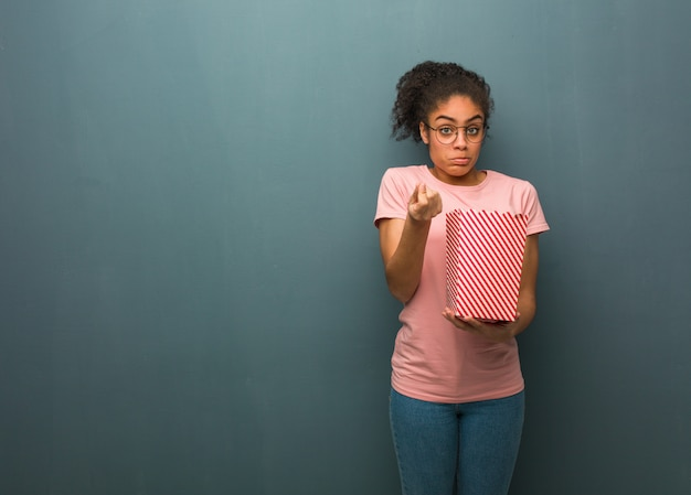 Young black woman doing a gesture of need. she is holding a popcorns bucket. Premium Photo