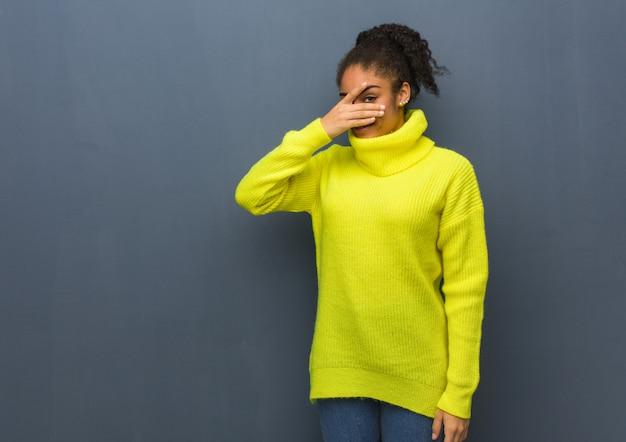 恥ずかしいと同時に笑っている若い黒人女性 Premium写真