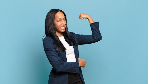 Young black woman feeling happy, satisfied and powerful, flexing fit and muscular biceps, looking strong after the gym. business concept Premium Photo