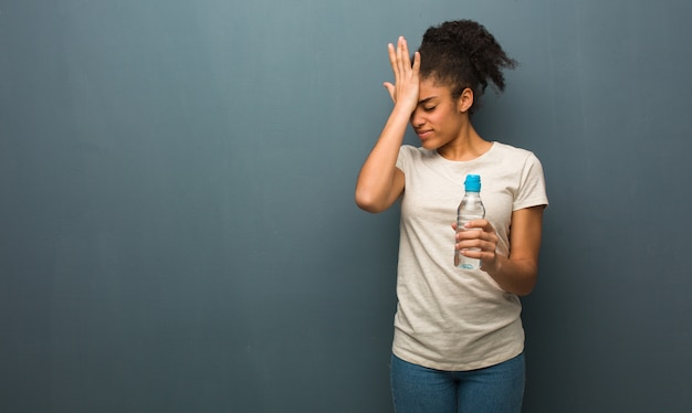 Young black woman forgetful, realize something. she is holding a water bottle. Premium Photo