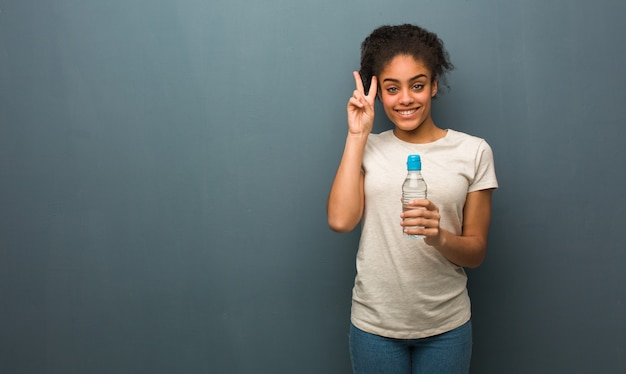 Young black woman fun and happy doing a gesture of victory. she is holding a water bottle. Premium Photo