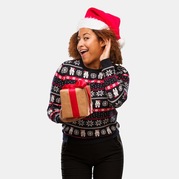 Young black woman holding a gift in christmas day try to listening a gossip Premium Photo