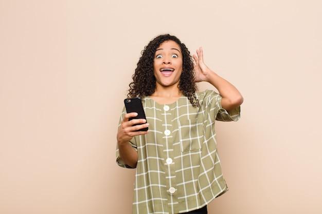 Молодая негритянка кричит с поднятыми вверх руками, чувствуя ярость, разочарование, стресс и расстроен с помощью смартфона Premium Фотографии