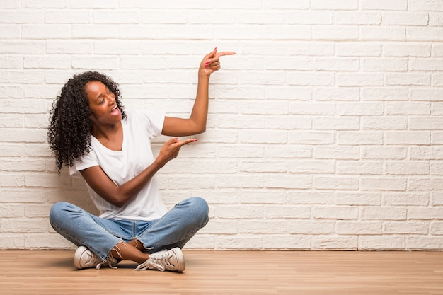 Young black woman sitting on a wooden floor pointing to the side Premium Photo