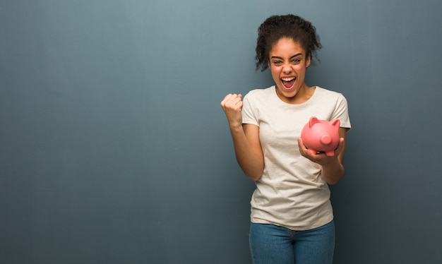 Young black woman surprised and shocked. she is holding a piggy bank. Premium Photo