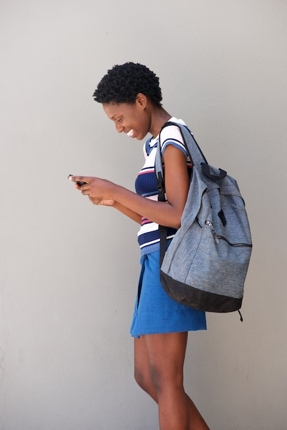 Young black woman walking and using cell phone on gray background Premium Photo