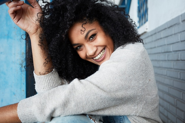 Young black woman with afro hair laughing and enjoying Free Photo