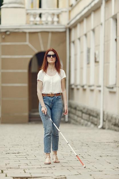Giovane cieco con bastone lungo che cammina in una città Foto Gratuite