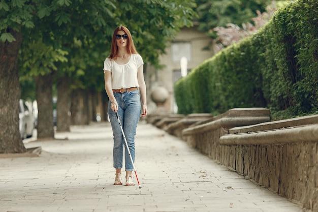 街を歩いて長い杖を持つ若い盲人 無料写真